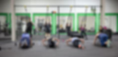 A mixed ability fitness class performing pull ups and press ups in front of a Personal Trainer