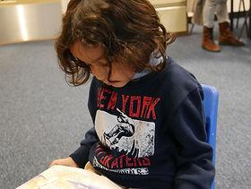 Child reading in creche.