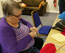 Knitting with red wool at Chat & Charity, Encounter Centre