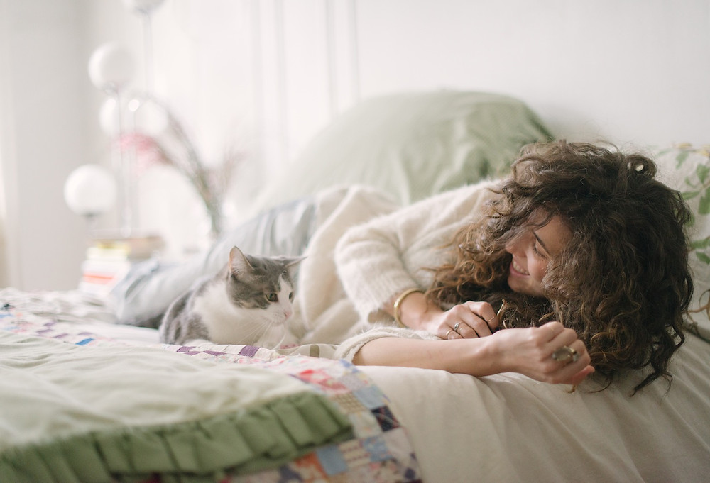 Cat Photography in New York. Curling up together on the bed with her cat.