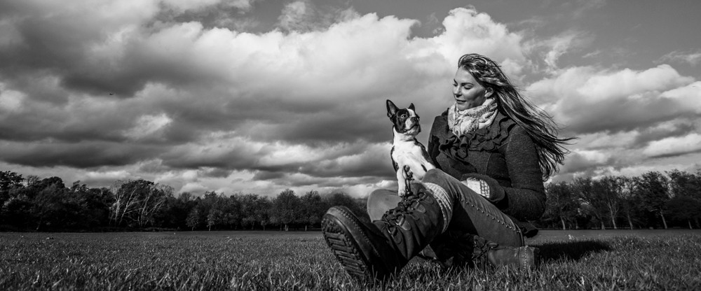 London Dog Photography. Elvis the Boston Terrier with his owner Debbie on Wandsworth Common. Black and white.