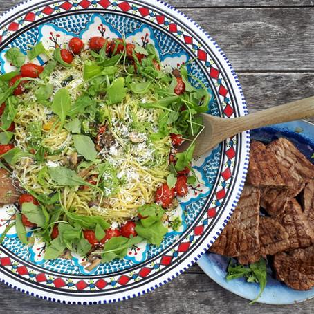 Pasta pesto met gestoofde groentjes en paddenstoelen en gegrilde steak