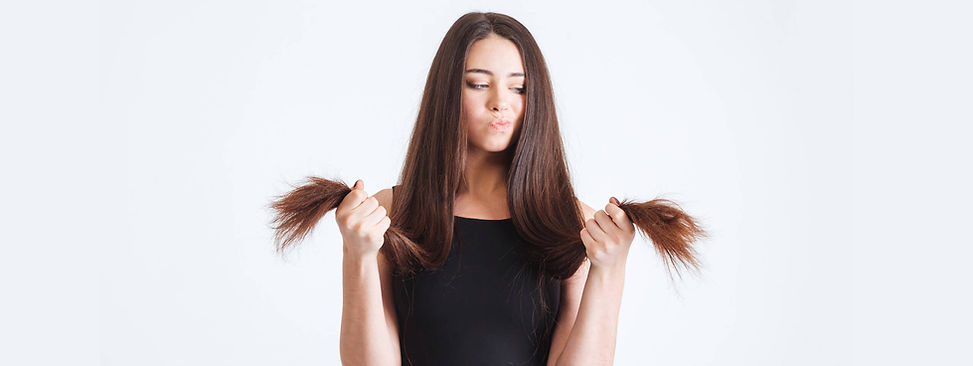 woman-examines-dry-split-ends-of-hair.jp