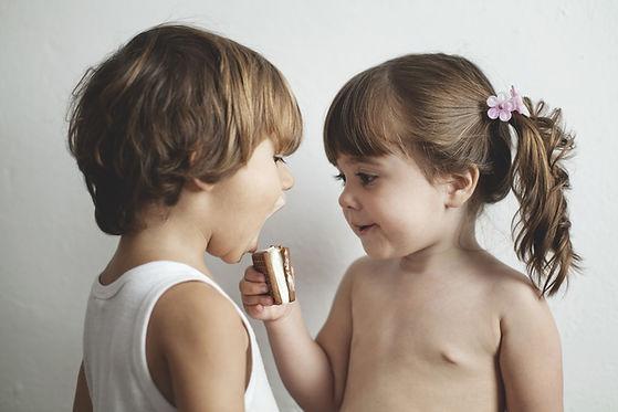 Zwei Kinder beim Essen einer Waffeln mit Marshmallowfüllung