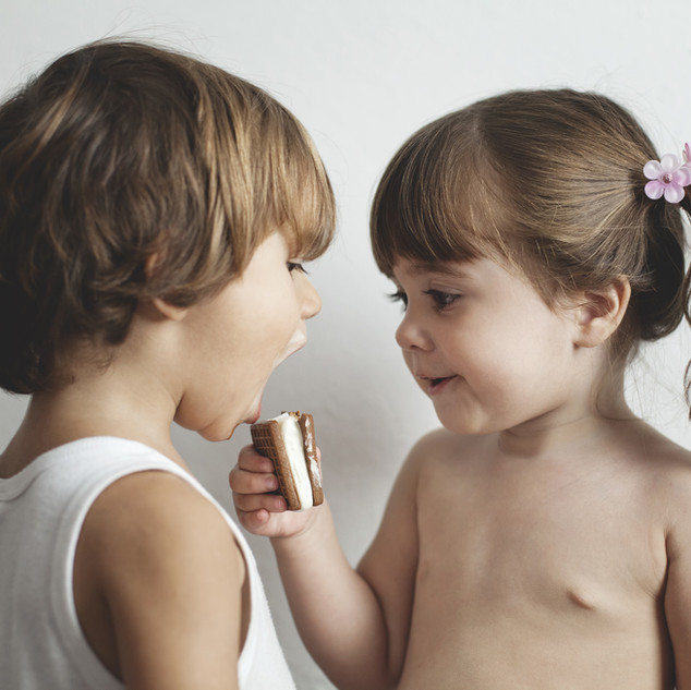 Small girl offering biscuit to small boy