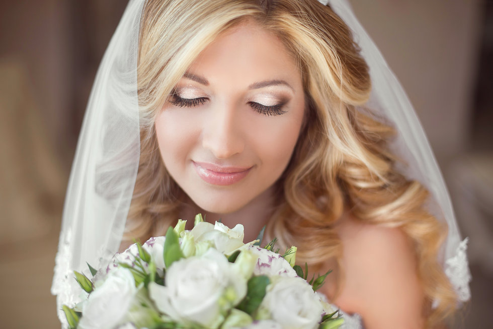 Beautiful bride with wedding bouquet of flowers. Makeup. Blond curly hairstyle. Smiling yo