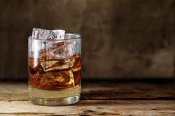 glass-scotch-whiskey-with-ice-on-a-rustic-wooden-table-000085209585_Large