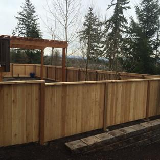 Solid cedar fence with top rail.