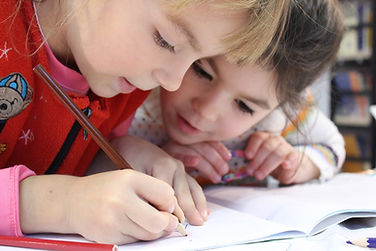 Two girls are drawing or writing. One girl watches the other girl with joint attention and a curious, interested look.