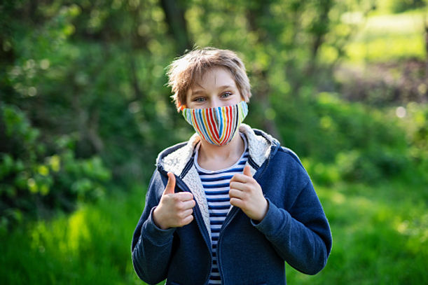 kid with rainbow mask thumbs up in fores