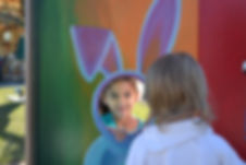 Two children are playing, looking at each other though a rabbit cut-out at the fair or circus. One girl has a shy smile.