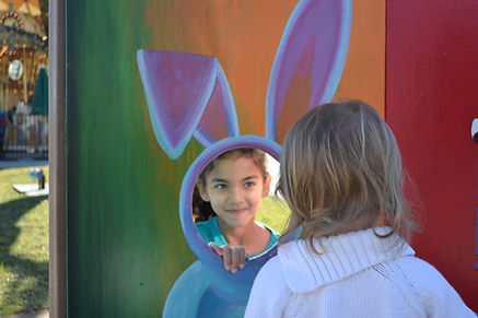 Girl playing on outing, pretend play at carnival, shy smile, social initiation, social skills therapy, eye contact, greetings, peer play
