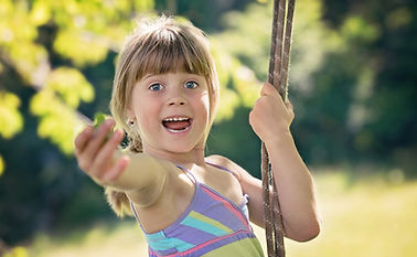 A girl is smiling, happy and excited on a rope swing, reaching her hand out.