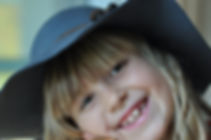 A girl is smiling, wearing a hat, with a happy expression.