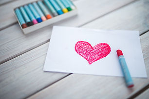A red heart drawn with a red crayon on a whit paper, with multiple crayons of different colors in the background.