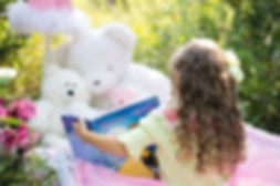 A young girl is doing pretend play and perspective taking, reading the fairy tale Beauty and the Beast to her stuffed animal bear family.