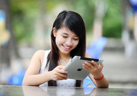 Teen girl joyfully reading on iPad, engaged in learning.