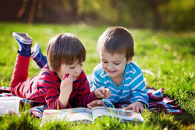 two-boys-happy-reading-books-in-grass-ou