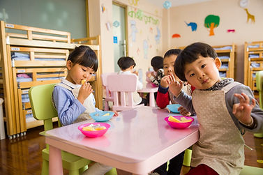 Preschool or kindergarden children are eating fruit for snack at the table.