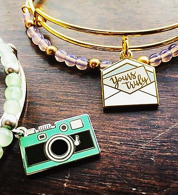 Camera and Letter jewelry designed by Emily Lopuch for Alex and Ani.