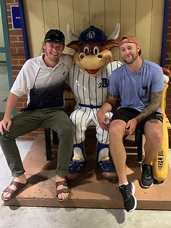 Two men with baseball hats on. Smiling next to a statue of the Durham Bulls mascot.