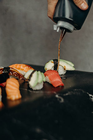 person-putting-sauce-on-a-sushi-dish-333