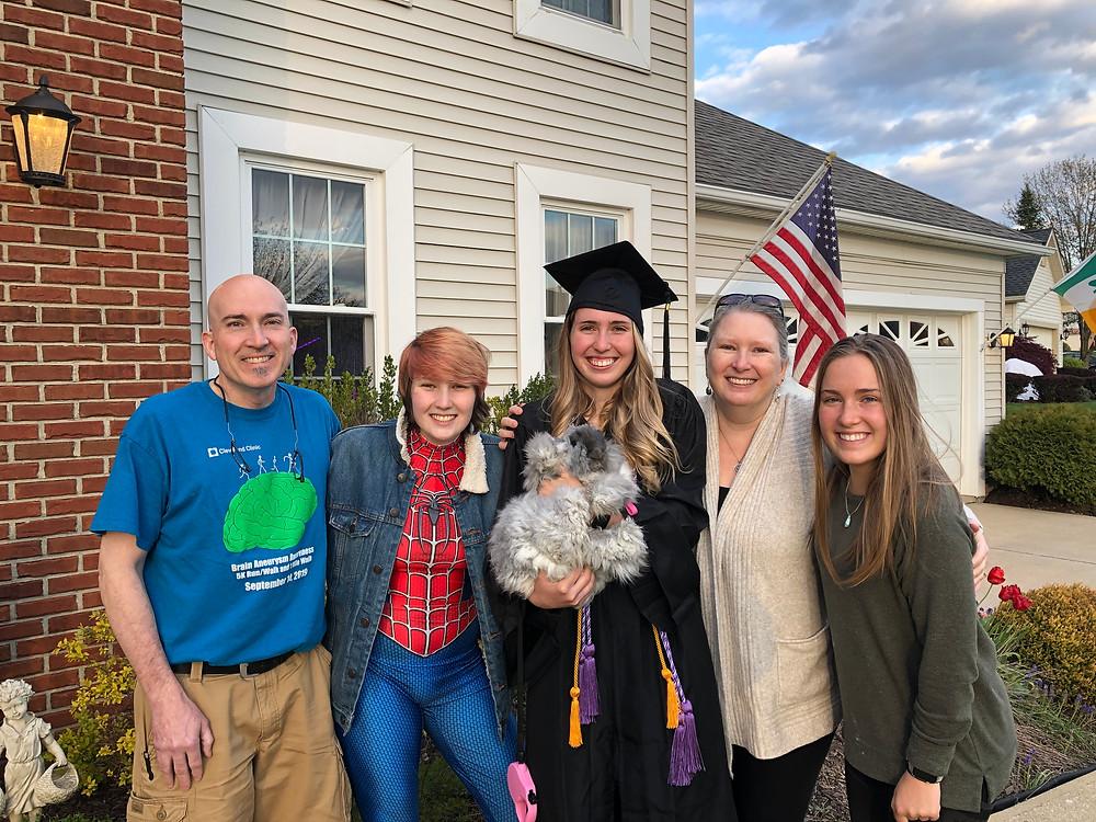 A smiling family celebrating a graduation.
