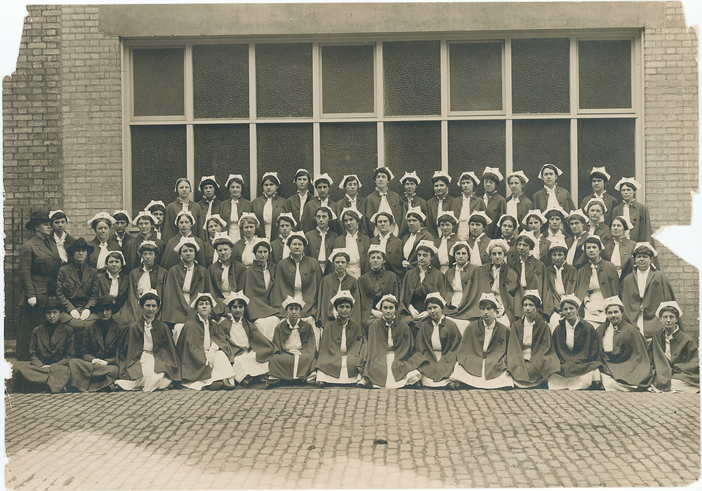 A black and white photo of a group of nurses from the early 1900s in front of a brick building with windows.