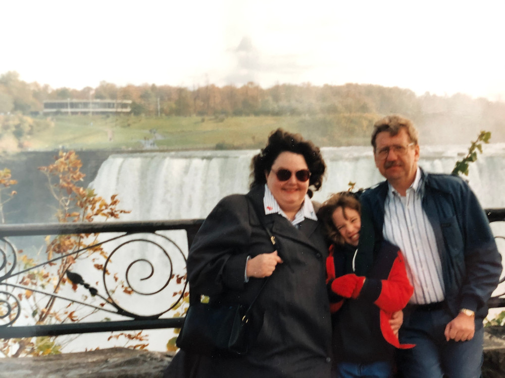 Parents and child standing in front of Niagara Falls.