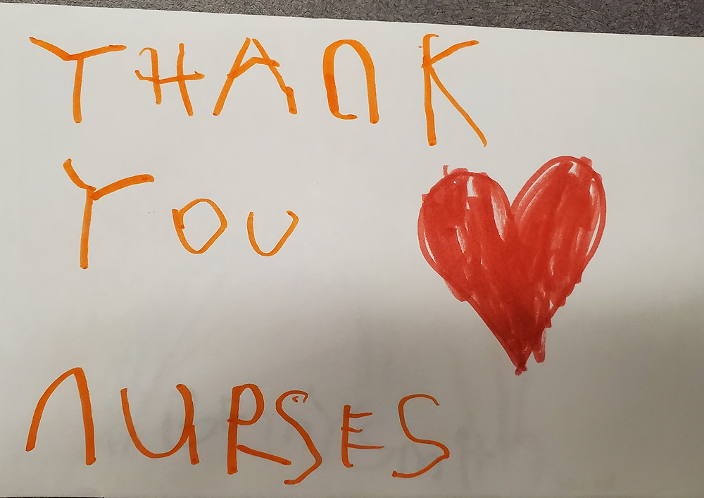 "A child's handwritten card saying ""Thank You Nurses"" with a heart.s"""