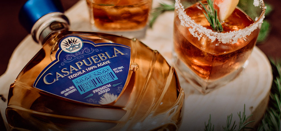 Close up of CasaPuebla Añejo Tequila label with cocktail