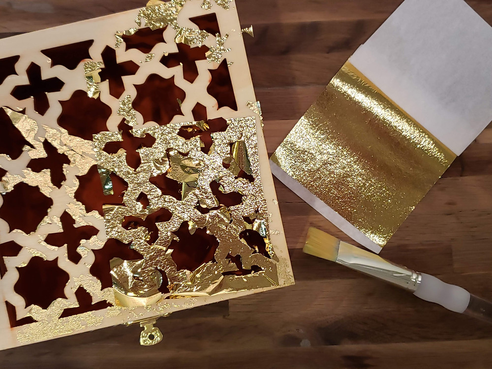 Brush gold leaf onto tacky surface.