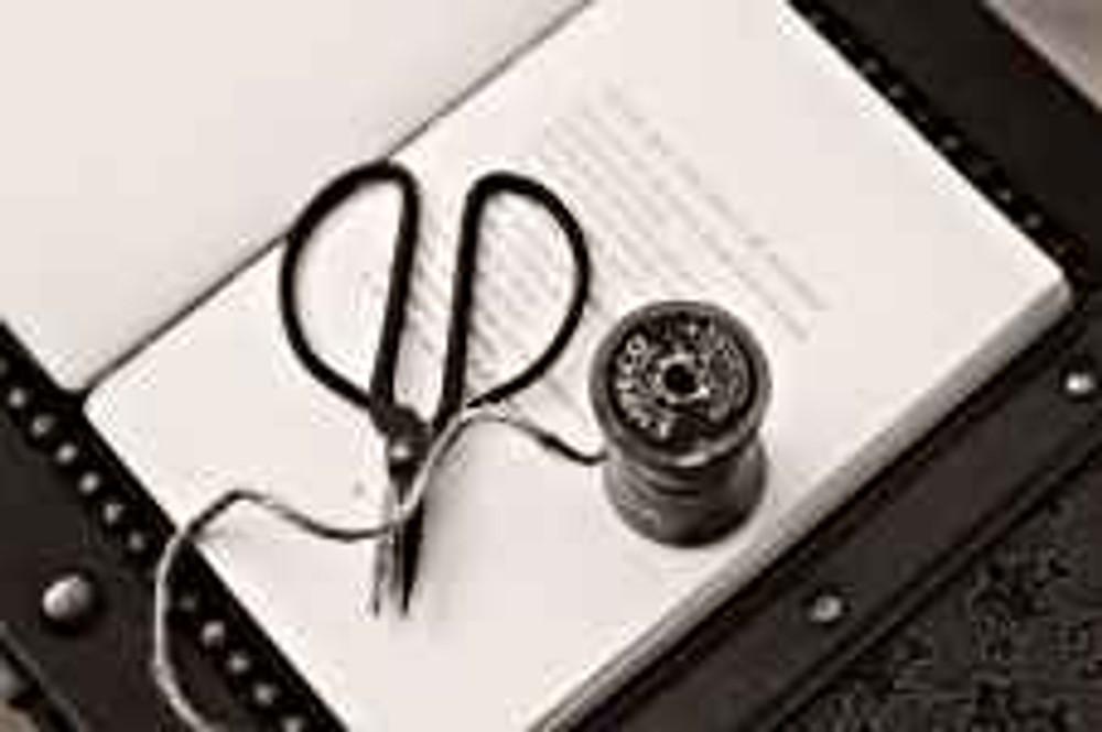 black scissors near thread reel on white book page
