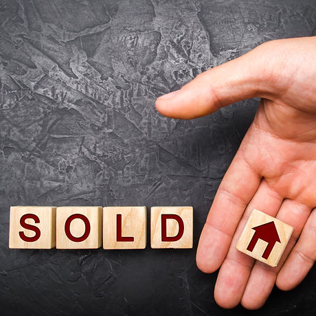 realtor's hand puts a cube with a picture of the house to the word sold. Concept of selling a house,