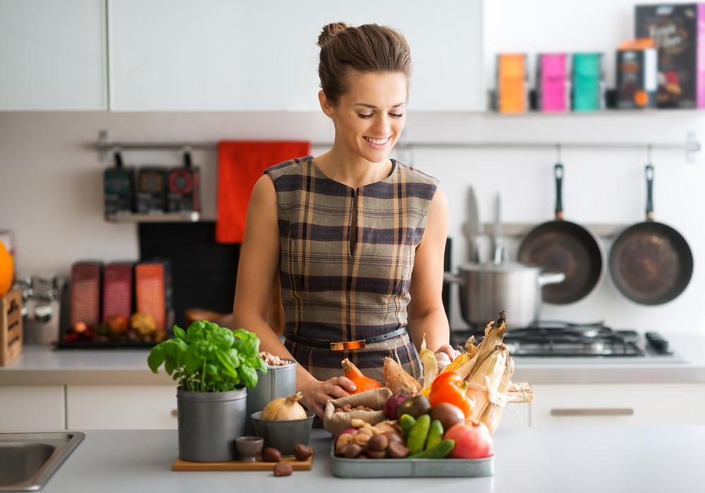 woman smiling in the kitchen surrounded by vegetables