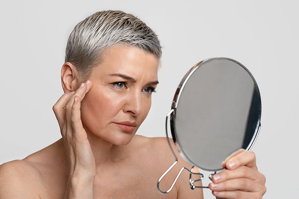 skin aging mature woman looking in the mirror