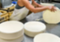 Cheese Maker Putting Young Gruyere Comte