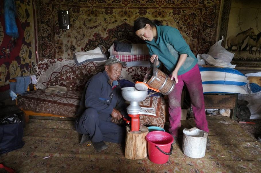 Mongolische Familie bei der Butterherstellung