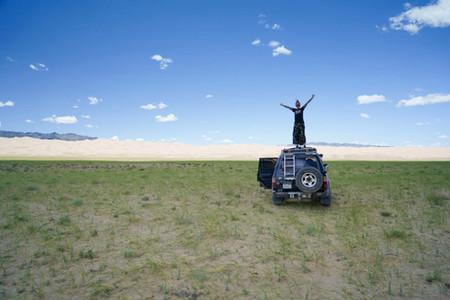 Kati posiert auf Auto vor Sanddünen