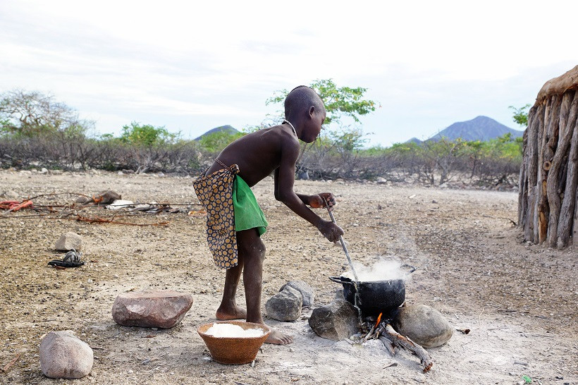 "Kleiner Himba Junge, der ""Pap"" kocht"
