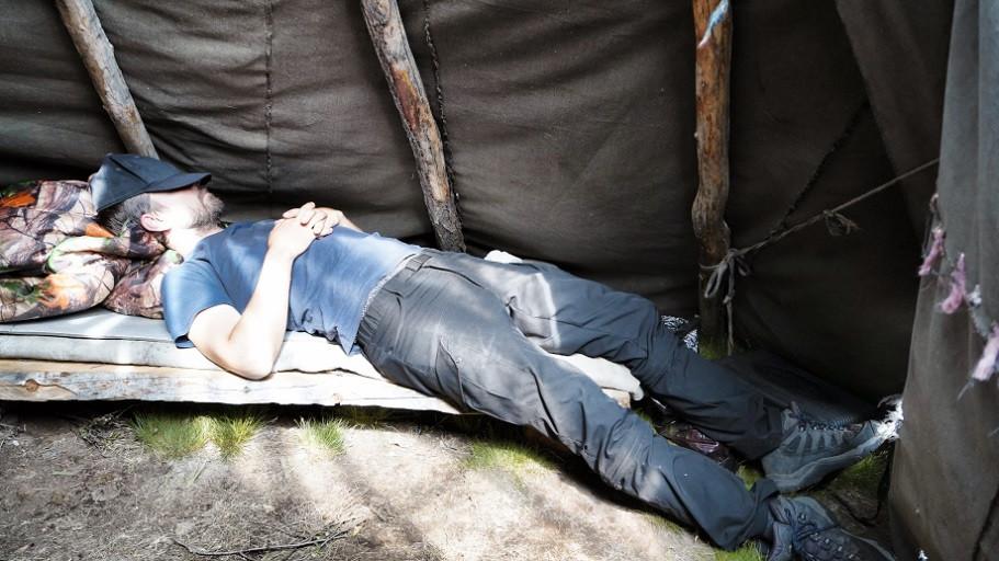 Hermann schläft auf Holzbett im Tipi