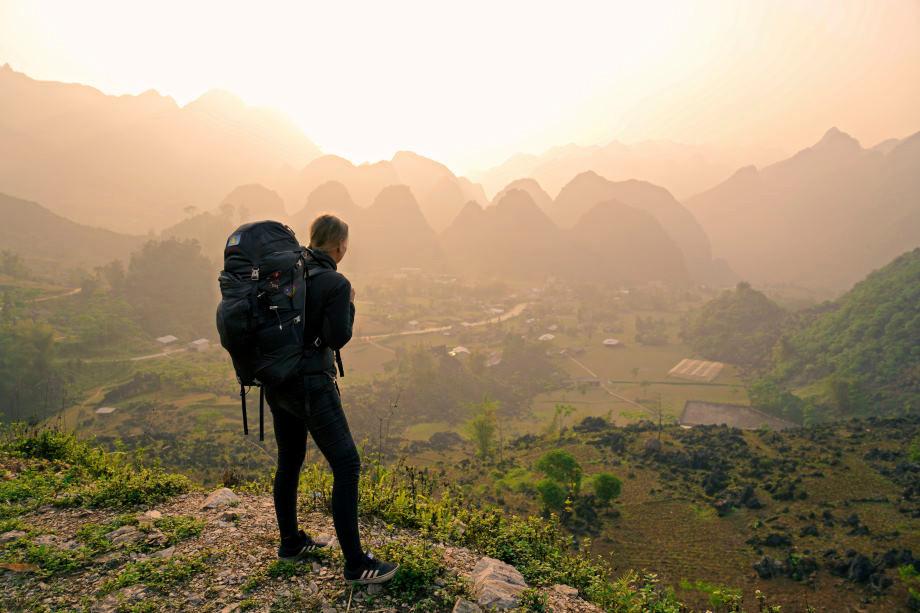 Kati blickt auf ein Tal mit Karstbergen am Horizont