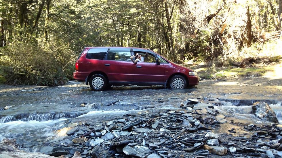 Kati im Auto in einem Flussbett in Neuseeland