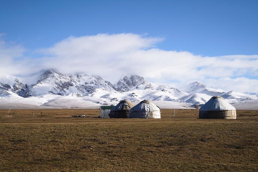 Jurten vor schneebedeckten bergen in Kirgisistan
