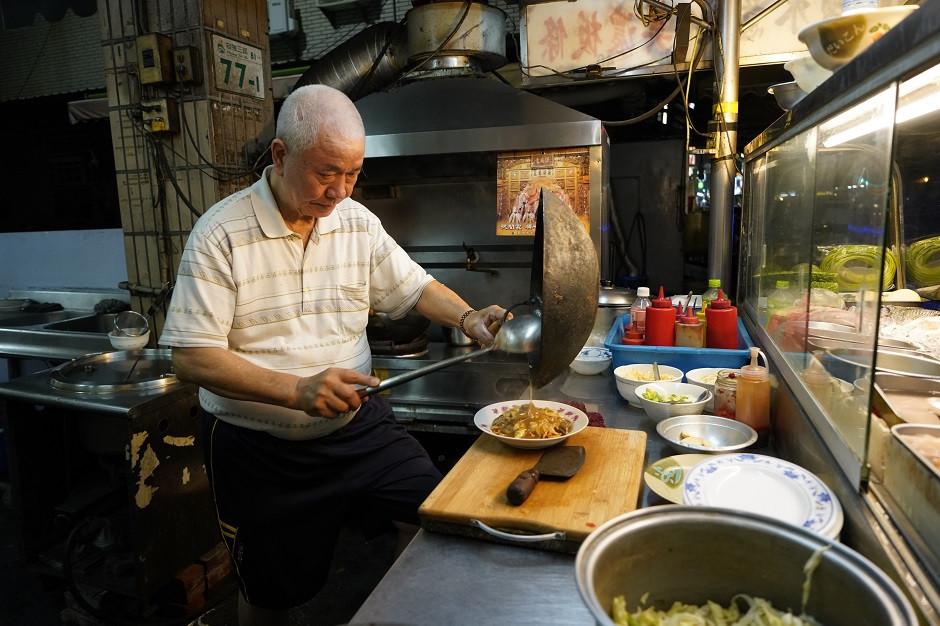 Mann kocht an Streetfood Stand in Taiwan