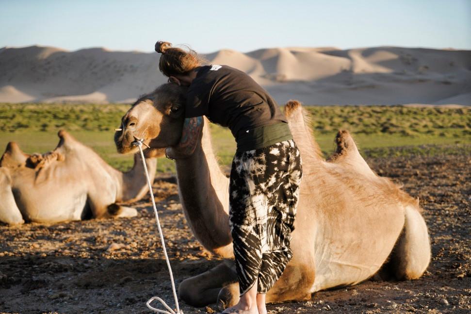 Kati umarmt ein Kamel in der Mongolei