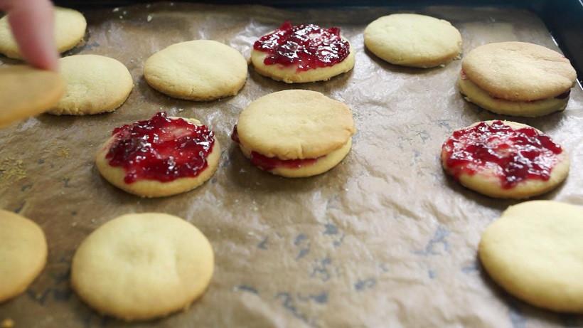 Hälfte der Kekse mit Marmelade bestreichen
