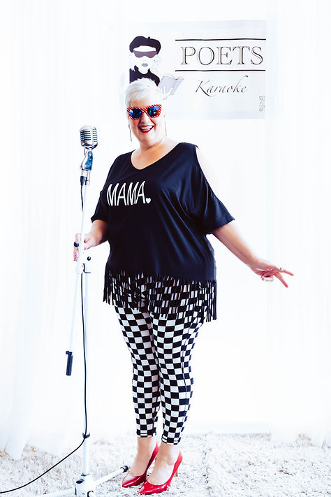 Karaoke host Mama Dots posing with her Elvis style microphone on a white background with the POETS Karaoke banner behind her