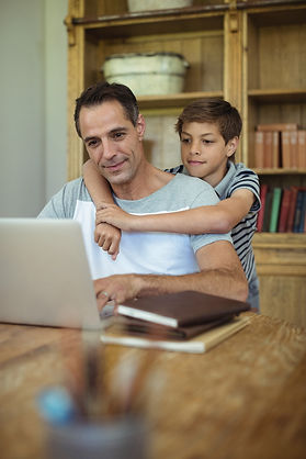 father-and-son-using-laptop-in-study-roo