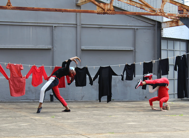 Two performers dance with clothes hanging in the background